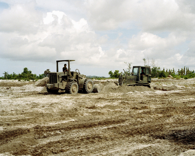 Seabees use a front loader, left, and a bulldozer to consolidate piles of volcanic ash during cleanup of the ash that fell on the naval station following the eruption of Mount Pinatubo.