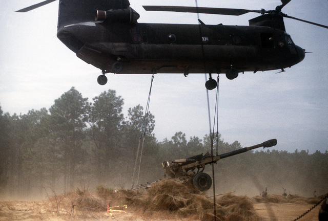 A C Battery, 1ST Battalion, 10th Marine Regiment, 2nd Marine Division, M-198 155mm howitzer is delivered to a landing zone by an Army CH-47D Chinook helicopter during the joint service artillery exercise Express Sword