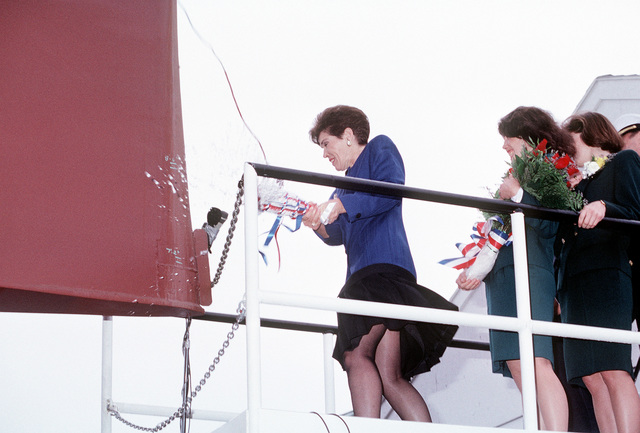 Connie Jeremiah breaks a bottle of champagne across the bow to the guided missile destroyer JOHN PAUL JONES (DDG-53) to christen the ship prior to its launch. Mrs. Jeremiah, the ship's sponsor, is the wife ADM David E. Jeremaih, vice chairman of the Joint Chiefs of STAFF. The Jeremiah's daughters Kirsta, second from right, and Jodi, right are Mrs. Jeremiah's maids of honor for the ceremony