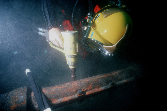 A diver of Underwater Construction Team 2 (UCT-2) uses an underwater impact wrench to tighten bolts on installed split pipe used to protect cable on the ocean floor. UCT-2, of Port Hueneme, California, is repairing cable off the coast of the island