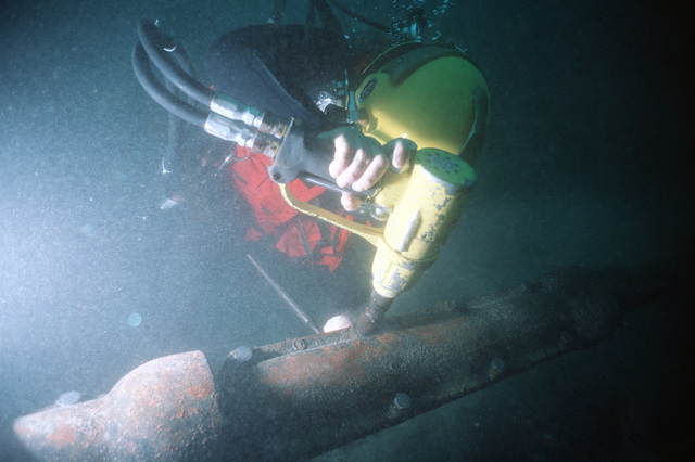 A diver of Underwater Construction Team 2 uses and underwater impact wrench to tighten bolts on installed split pipe used to protect cable on the ocean floor. UCT-2, of Port Hueneme, California, is repairing cable off the coast of the island