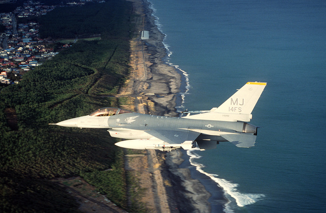 An F-16C Fighting Falcon aircraft of the 14th Fighter Squadron flies over the coastline near Misawa Air Base. The aircraft is armed with AIM-9 Sidewinder missiles.