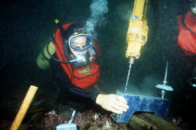 Two divers of Underwater Construction Team 2 (UCT-2) use an underwater hydraulic impact drill to stablize a cable to a rock head on the ocean floor. UCT-2, of Port Hueneme, California, is repairing underwater cable off the coast of the island