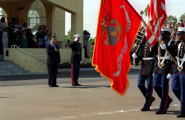 Congressman Martinez, with his hand over his heart, standing next to a Marine officer, who is wearing dress blues and giving a hand salute, in front of the reviewing stand while a Marine color guard passes in review