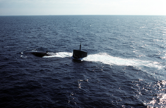 The bow and sail of the nuclear-powered attack submarine USS PHOENIX (SSN 702) rise out of the water as the submarine comes to the surface