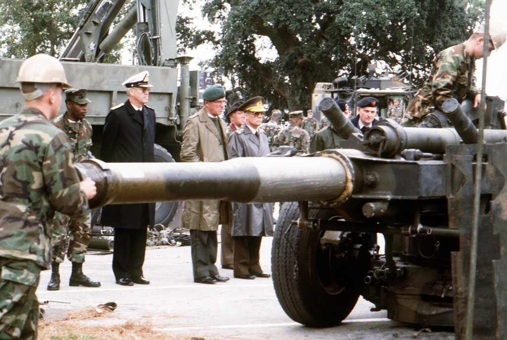 A group of visiting officers from Supreme Headquarters, Allied Powers, Europe (SHAPE) watch as members of the 2nd Marine Division assemble an M-198 155mm howitzer