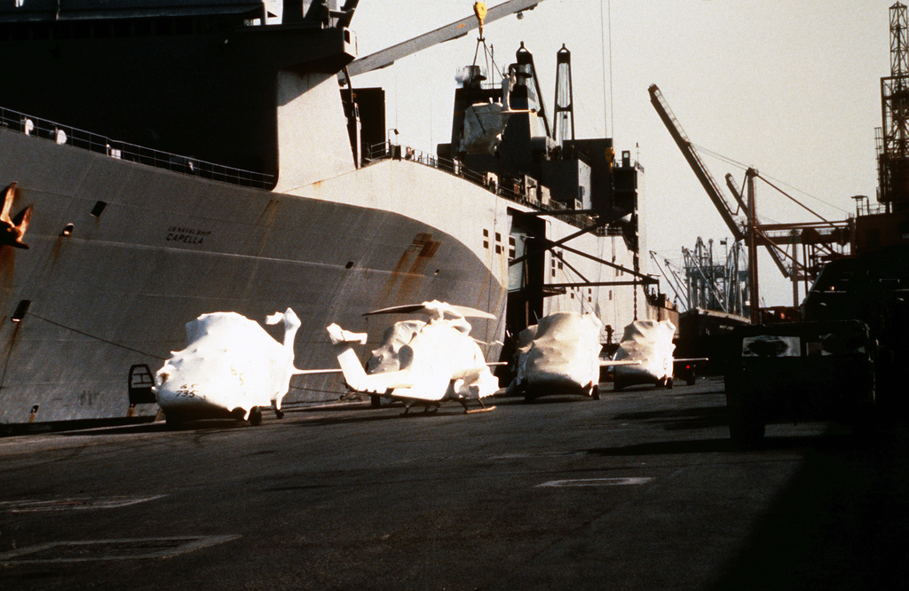 UH-60 Black Hawk (Blackhawk) and AH-1 Cobra helicopters are loaded aboard the rapid-response vehicle cargo ship USNS CAPELLA (T-AKR-293) for transportation back to Germany in the aftermath of Operations Desert Shield/Desert Storm. The helicopters are encased in protective plastic for shipping