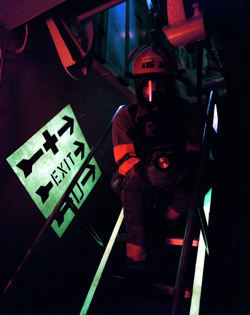 PO3 Walter Graham pauses on a ladder while entering a darkened compartment aboard the aircraft carrier USS JOHN F. KENNEDY (CV 67) during a damage control drill. Photoluminescent paint like that used on the sides of the ladder and on the exit sign has been applied throughout the ship to help personnel move about in low-light conditions.