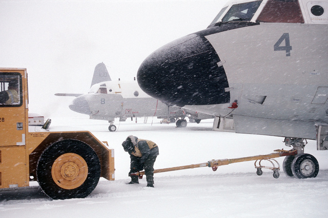 Crewmen position a tractor to tow a P-3 Orion anti-submarine aircraft during a New England snow storm