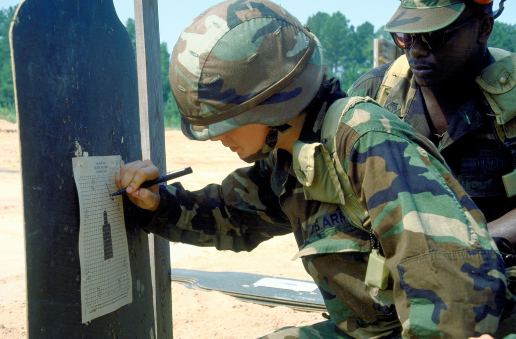 A soldier plots out hits on a target sheet while practicing on the rifle range during basic training