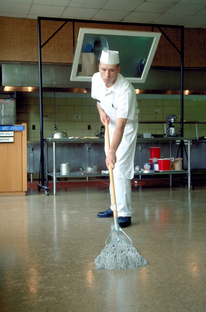 A student in the food service course mops the kitchen floor during advanced individual training