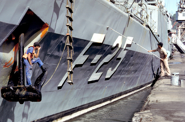 Crew members paint the hull of the Venezuelan frigate GENERAL SALOM (F-25) while the ship is in port during Unitas XXXII, a combined exercise involving the naval forces of the United States and eight South American nations
