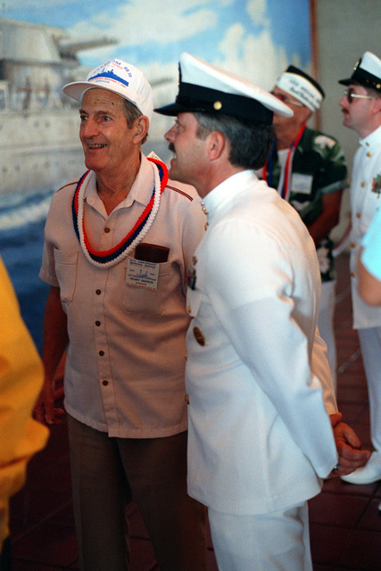 MASTER Cheif Aerographer's Mate Steve Walton escorts USS ARIZONA survivor Henry Davison at the USS ARIZONA Memorial Visitors Center during 50th anniversary Remembrance Day ceremonies. Davison was the officer of the deck on Dec. 7, 1941, when the Japanese bombed Pearl Harbor and sank the USS ARIZONA