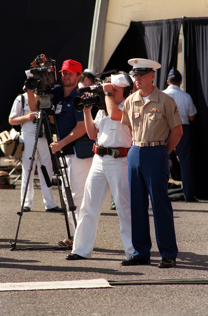 Photographer's Mate 2nd Class Dan Smith, center, and another cameraman videotape the audience at the USS ARIZONA Memorial Visitors Center during Survivor's Day ceremonies honoring the sailors and Marines of the battleships that were sunk or damaged in the Dec. 7, 1941, attack on Pearl Harbor