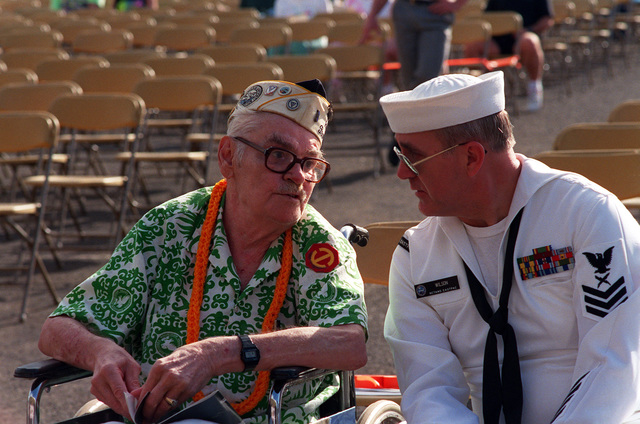 Raymond Sandlin, an Army Air Corps private who survived of the Dec. 7, 1941, attack on Pearl Harbor, listens to the U.S. Pacific Fleet Band with his escort, PO1 F. Scott Wilson, during Remembrance Day ceremonies at the USS ARIZONA Memorial Visitors Center. The event commemorates the 50th anniversary of the bombing