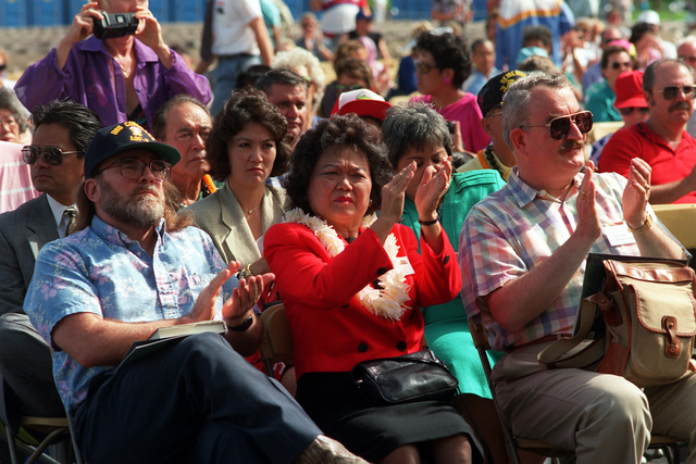 Rep. Patsy Mink and the audience applaud during Remembrance Day ceremonies at the USS ARIZONA Memorial Visitors Center. USS ARIZONA survivors are honored during the commemoration of the 50th anniversary of the Dec. 7, 1941, attack on Pearl Harbor