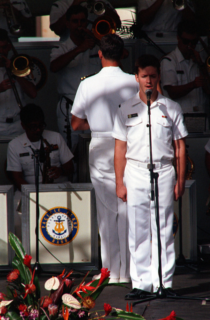 "SA Norbert ""Bert"" Morgan of the U.S. Pacific Fleet Band sings the Navy Hymn during Remembrance Day ceremonies at the USS ARIZONA Memorial Visitors Center. The event honors USS ARIZONA survivors on the 50th anniversary of the Dec. 7, 1941, attack on Pearl Harbor"