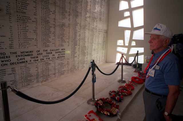 USS ARIZONA crew member Frances M. Falge gazes at USS ARIZONA Memorial wall engraved with the names of his shipmates who perished during Dec. 7, 1941, attack on Pearl Harbor. He and other USS ARIZONA survivors are on a private tour of the memorial following 50th anniversary Remembrance Day ceremonies