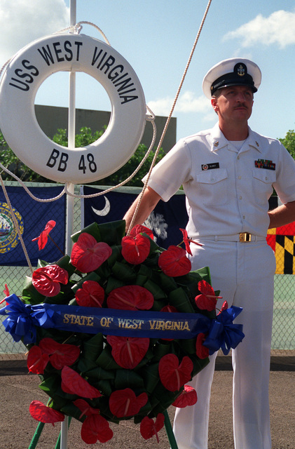 CPO Terry Clancy stands by the memorial wreath for the USS WEST VIRGINIA (BB-48) during Survivor's Day ceremonies at the USS ARIZONA Memorial Visitors Center. The event honors the sailors and Marines of the battleships that were sunk or damaged in the Dec. 7, 1941, attack on Pearl Harbor
