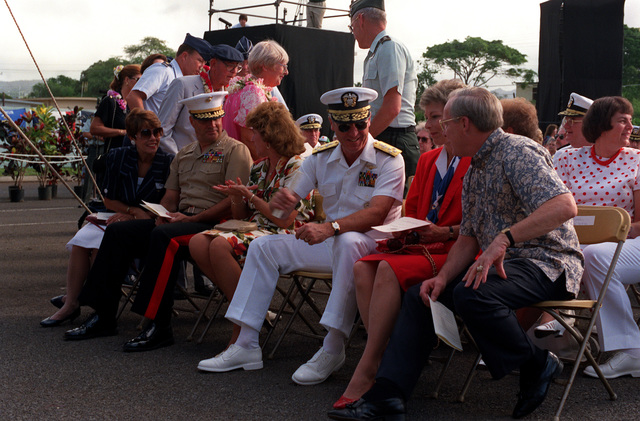 Front row guests LGEN Royal N. Moore, Commanding General, 3rd Marine Aircraft Wing; ADM Robert J. Kelly, Commander in CHIEF, U.S. Pacific Fleet; and Secretary of the Navy H. Lawrence Garrett III and their wives chat before Survivor's Day ceremonies at the USS ARIZONA Memorial Visitors Center. The event honors the sailors and Marines of the battleships that were sunk or damaged in the Dec. 7, 1941, attack on Pearl Harbor