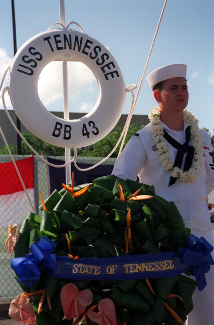 PO2 Ric Walker stands by the memorial wreath for the USS TENNESSEE (BB-43) during Survivor's Day ceremonies at the USS ARIZONA Memorial Visitors Center. The event honors the sailors and Marines of the battleships that were sunk or damaged in the Dec. 7, 1941, attack on Pearl Harbor