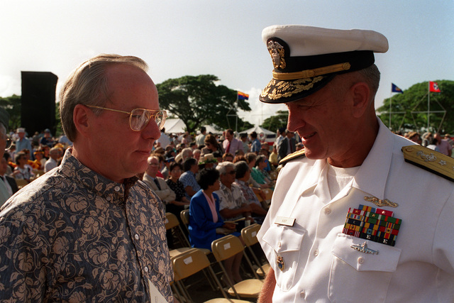 Secretary of the Navy H. Lawrence Garrett III speaks with RADM Larry G. Vogt, director for plans and policy, Commander in CHIEF, U.S. Pacific Fleet, during Survivor's Day ceremonies at the USS ARIZONA Memorial Visitors Center. The event honors the sailors and Marines of the battleships that were sunk or damaged in the Dec. 7, 1941, attack on Pearl Harbor