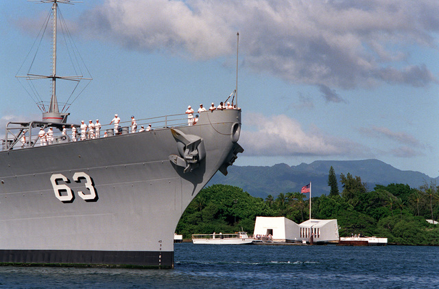 The USS MISSOURI (BB-63) arrives in port on Survivor's Day, when the sailors and Marines of the battleships that were sunk or damaged in the Dec. 7, 1941, attack on Pearl Harbor are honored. In the background is the USS Arizona Memorial, under which rests the sunken ship and the tomb of most of its crew