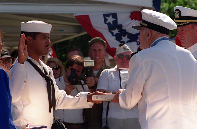 CAPT Donald K. Ross, USN (Ret.), a survivor of the Japanese attack on Pearl Harbor and a Medal of Honor recipient, re-enlists PO Don Bray during the dedication of the USS NEVADA Memorial at Hospital Point. The ceremony is taking place as part of an observance commemorating the 50th anniversary of the Japanese attack