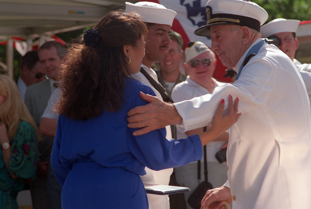 CAPT Donald K. Ross, USN (Ret.), a survivor of the Japanese attack on Pearl Harbor and a Medal of Honor recipient, converses with Mrs. Bray after re-enlisting her husband, PO Don Bray. The re-enlistment took place during the dedication of the USS NEVADA Memorial at Hospital Point, part of an observance commemorating the 50th anniversary of the Japanese attack