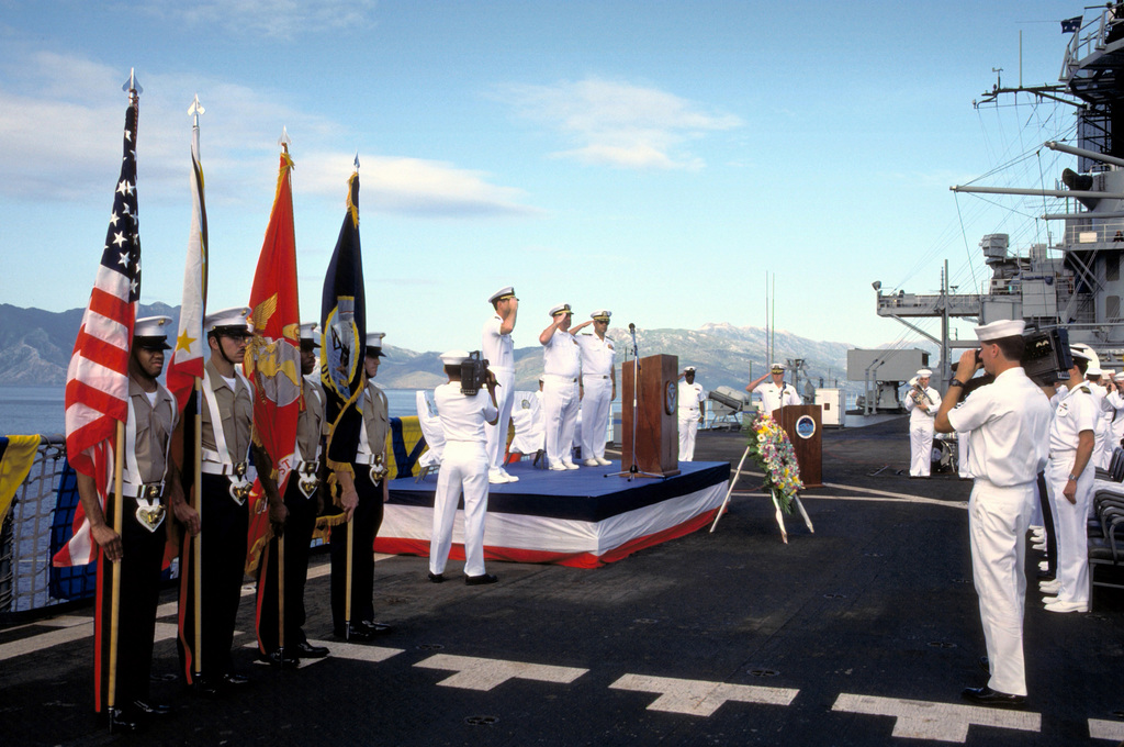 VADM Stanley R. Arthur, center, commander, U.S. Seventh Fleet, and two other officers salute from the speakers platform during a ceremony aboard the amphibious command ship USS BLUE RIDGE (LCC-19). The ceremony is being held to mark the 50th anniversary of the Japanese attack on Pearl Harbor