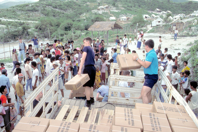 Sailors from the guided missile cruiser USS MOBILE BAY (CG-53) unload cases of meals, ready-to-eat (MREs) from the back of a truck.The sailors, all volunteers, traveled to three relocation centers to distribute food to Filipinos forced from their homes by the eruption of Mount Pinatubo