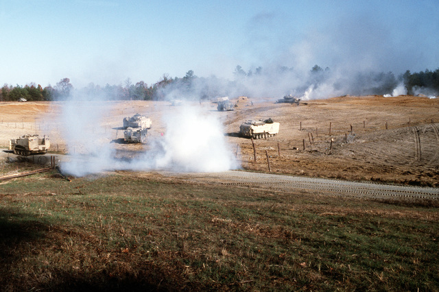 Elements of B Company, 2nd Combat Engineer Battalion (CEB), 2nd Marine Division, advance through a mechanical assault range during a training exercise. The vehicles include two M-9 armored combat earthmovers, four AAV-7A1 amphibious assault vehicles and two M-1A1 Abrams main battle tanks. The two AAV-7A1s in the foreground are fitted with mine clearance kits (MCSKs)