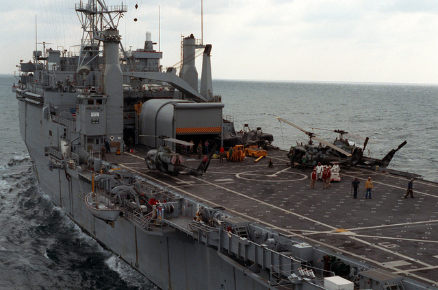 AH-1 Sea Cobra helicopters and a UH-1 Iroquois helicopter stand on the flight deck of the amphibious transport dock USS NASHVILLE (LPD-13) as the vessel is underway during maritime interdiction operations