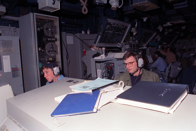 LT Phil Pardue, weapons officer, and Operations SPECIALIST SEAMAN Dave McColley monitor equipment aboard the guided missile cruiser USS TICONDEROGA (CG-47) as the vessel undergoes a simulated attack during maritime intrdiction operations