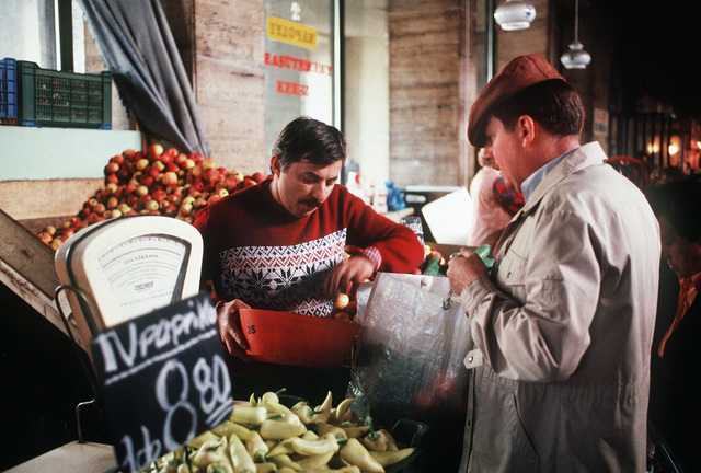 John Anderson selects produce at Budapest's central market. As husband of COL Ruth Anderson, the U.S. defense and air attache to Hungary, John maintains the household, shops, cooks and assists with their social calendar while his wife attends to her military duties