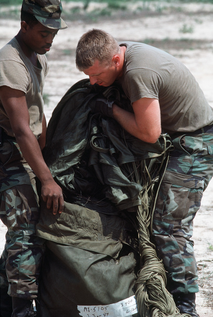 SRA Darrell C. Macklin, left, and SGT Michael D. Hawkins repack a parachute after an airdrop of supplies, part of a training session for the 3rd Mobile Aerial Port Squadron