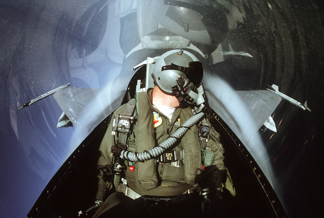 An F-16 fighter pilot turns to look for enemy aircraft while flying a training mission at the Maneuvering Instrumentation (ACMI) system range. The technologically advanced system digitally records combat maneuvers relayed by ACMI pods to computers at Homestead Air Force Base, Fla