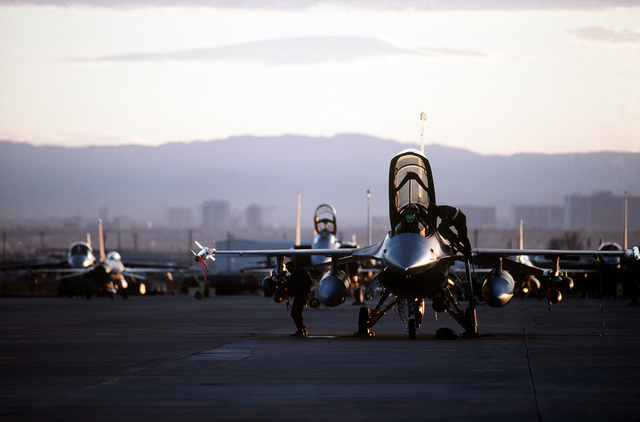 An F-16 Fighting Falcon aircraft is serviced on the flight line prior to flying a Desert Flag training mission. Designed by members of the 4440th Tactical Figher Training Group, the Desert Flag range introduces pilots to obstacles such as those encountered by fighter aircraft during Operation Desert Storm