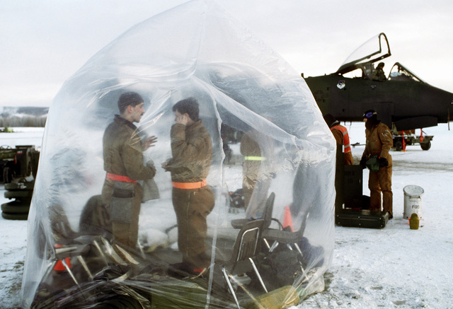 Members of the 343rd Aircraft Generation Squadron warm up in a heated plastic enclosure during Arctic Warrior '91 cold weather training