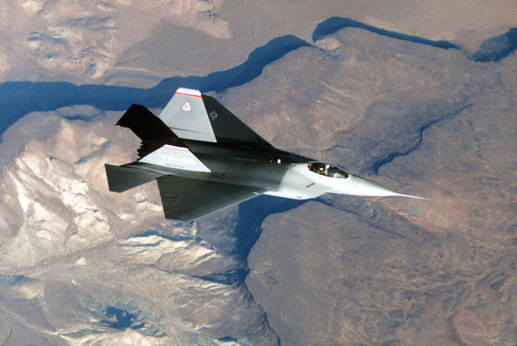An air-to-air overhead view of the YF-22 advanced tactical fighter aircraft during a test flight. The aircraft represents the latest developments in stealth or low observable technology.