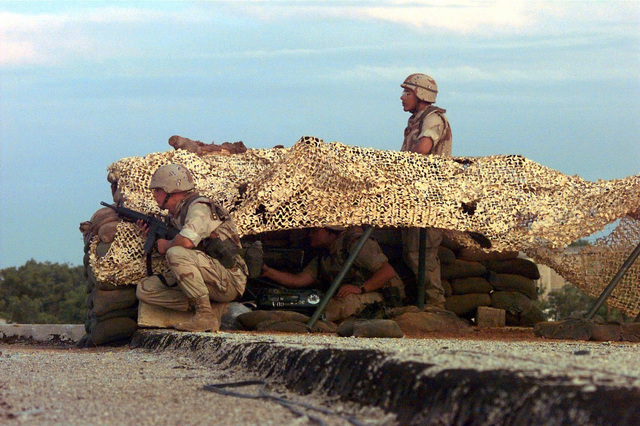 Left profile shot of three US Marines taken on the rooftop of the American School in Mogadishu, Somalia. They are in a netted desert camouflaged bunker. The Marine closest to the camera is crouched down and holds a M16 machine gun. The Marine in the center of the frame sits under the netting operating unidentifiable communications gear and the Marine to the right stands looking to his left. They are trying to pinpoint where sniper fire is coming from. The Marines are from the 3rd Battalion, 11th Marine Regiment of Twenty-nine Palms, California, and are in Somalia as part of the Joint Task Force conducting Operation Restore Hope