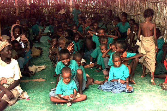 Straight on shot inside a bamboo hut at several Somali children sitting in rows on a green mat. Almost all of the children are wearing green t-shirts. Some older Somali women are seen sitting in a row at the left of the frame