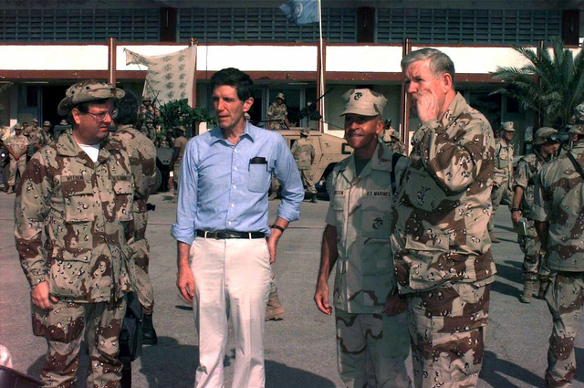 US Marine, LGEN Robert Johnston, Commander, Joint Task Force Operation Restore Hope, stands on the tarmac of Mogadishu Airport with US Congressman John Murtha, Democrat from Pennsylvania; to his left. Pennsylvania Congressman Curt Weldon stands at the left of the frame and Ambassador Robert Oakley is to Weldon's left. They're in Somalia to visit troops assigned to Operation Restore Hope