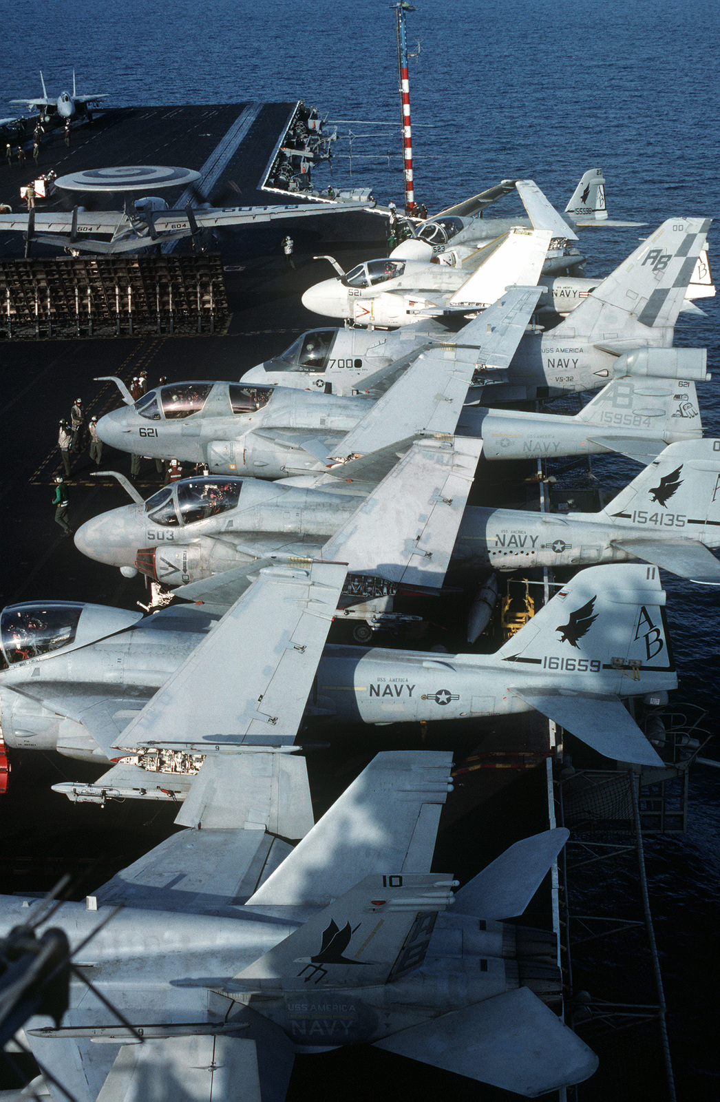 Various aircraft line the flight deck of the aircraft carrier USS AMERICA (CV 66). They include, from foreground: an F/A-18C Hornet aircraft, two Attack Squadron 72 (VA-72), A-6E Intruder aircraft, a Tactical Electronic Warfare Squadron 137 (VAQ-137) EA-6B Prowler aircraft, an Air Anti-submarine Squadron 32 (VS-32) S-3A Viking aircraft and two more VA-72 A-6E Intruder aircraft