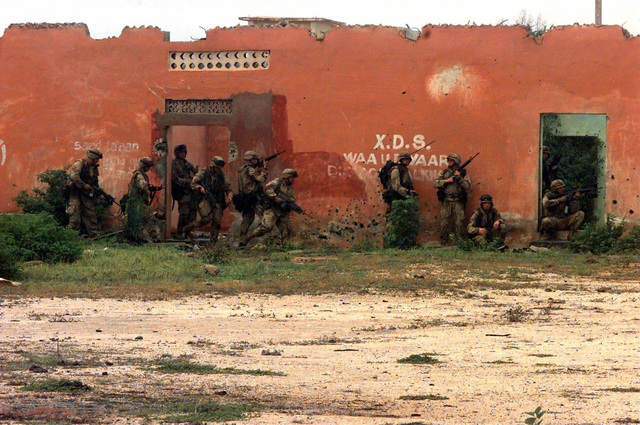 Ten US Marines walk along the side of a red clay colored building with their M16 rifles in the ready position. Some Marines are walking; others are kneeling or sitting in a doorway. The roof of the building appears to be missing. The Marines, from Task Force Mogadishu, have surrounded the weapons cantonment of Somali Warlord General Aideed in the northern part of the Captial City of Mogadishu. Their mission is in direct support of Operation Restore Hope