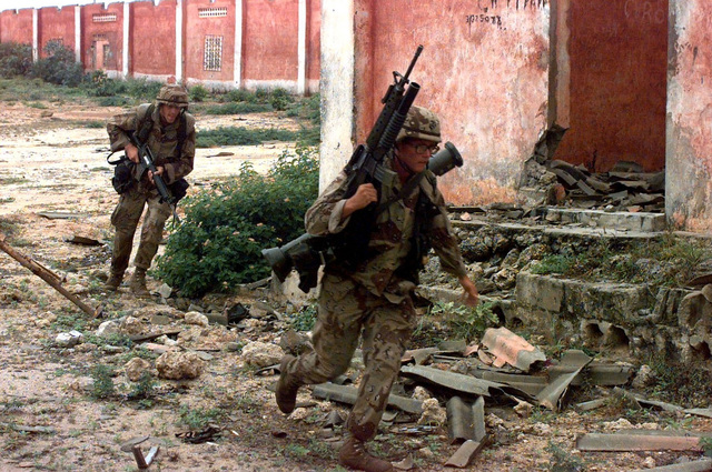 Two US Marines run toward the camera around a dilapidated building. The Marine in the foreground carries a M16A2 rifle with the M203 Grenade Launcher attached. Slung over his shoulder he has a M136 (AT4) light anti-armor weapon. The Marine in the background carries a M16A2 rifle pointed toward the ground. They are running for cover as sniper shots are fired from undisclosed areas of the cantonment area. The Marines are from Task Force Mogadishu. Their mission is in direct support of Operation Restore Hope