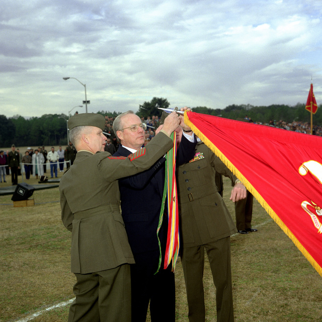 Secretary of the Navy H. Lawrence Garrett III, assisted by MAJ. GEN. F.X. Hamilton, commander, Marine Corps Logistics Base (MCLB), and SGT. MAJ. Richard Schuler, attacks the Meritorious Unit Commendation (MUC) ribbon to the organization color. Garrett awarded the Marines of the MCLB the MUC in recognition of their achievements during Operation Desert Storm