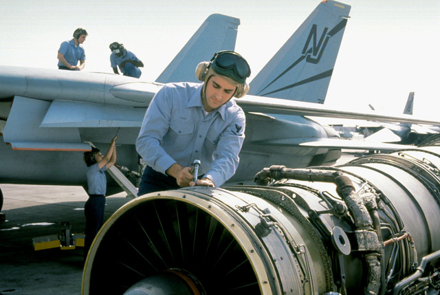 An airman works on the turbofan of a jet aircraft. Behind him, other maintenance crew members work on an F-14A Tomcat fighter aircraft of Miramar's Fighter Squadron 124 (VF-124)