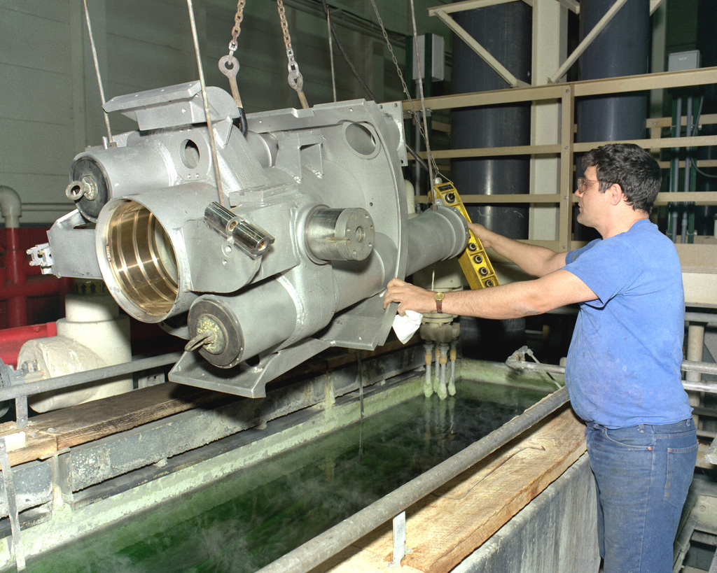 Larry Williamson prepares to lower the cradle assembly of an M-198 155mm howitzer into a phosphate plating tank at the Rock Island Arsenal