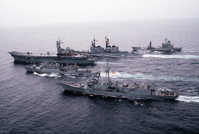 The guided missile destroyer USS SCOTT (DDG-995), second from the top, steams in battle group formation with four Spanish ships during joint operations. The Spanish ships are, from top to bottom; the fleet tanker MAR DEL NORTE (A-11), the aircraft carrier PRINCIPE DE ASTURIAS (R-11), and guided missile frigates ASTURIAS (F-74) and REINA SOFIA (F-84)